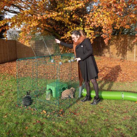 Eine Frau im Herbst im Freien mit zwei Kaninchen in einem Auslaufgehege